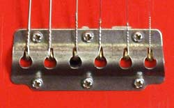 The very simple pressed-metal tailpiece is held to the body with six screws
