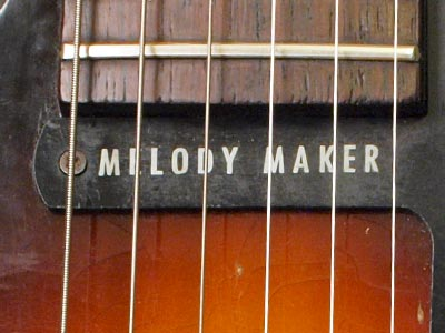 The scratchplate of this guitar has the words Melody Maker at the end of the neck