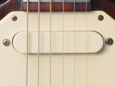 The cream coloured Gibson PU380 pickup is scratchplate mounted. The scratchplate of the Walnut finished SG-style Melody Makers was painted a cream colour to match